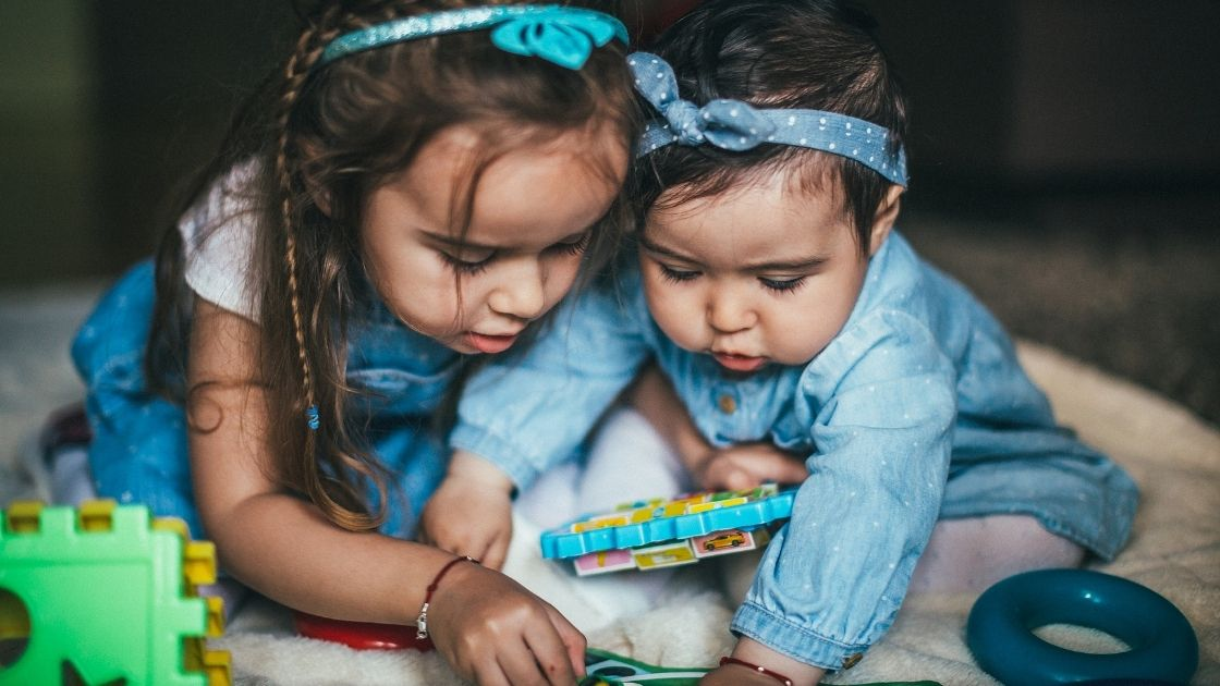 A baby and her older sister playing with toys
