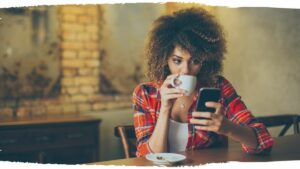 Woman drinking coffee shopping on her phone to buy ethical products.