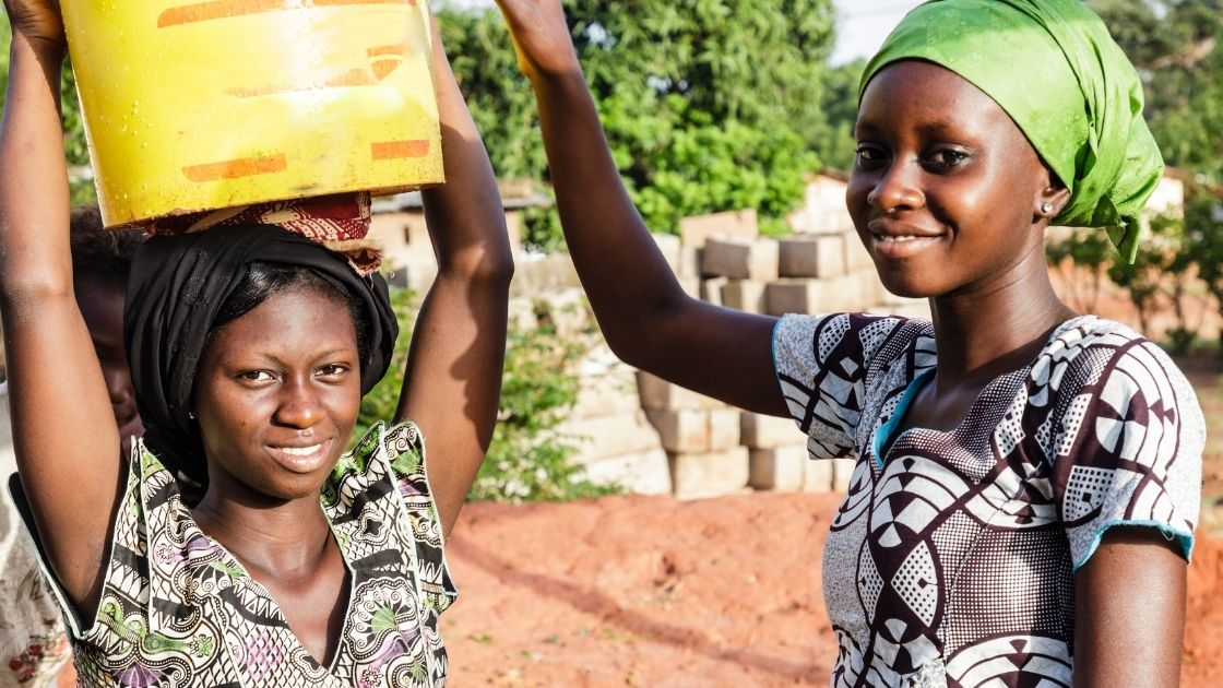 Women carrying water to provide their house with clean water.